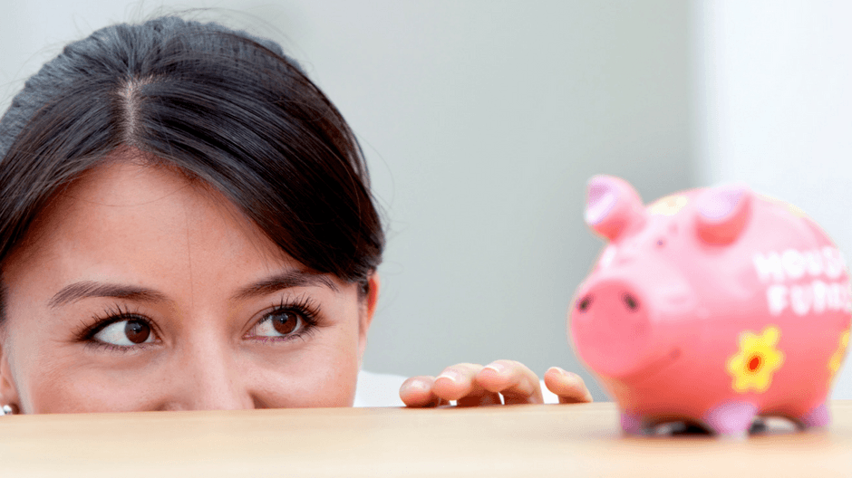 Woman peering over table at piggy bank